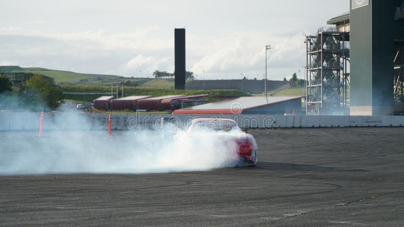 Racing car drift with smoking tyres. Drift racing, drifting car, street racing, smoking tyres and fast driving. Drift car in action stock photography