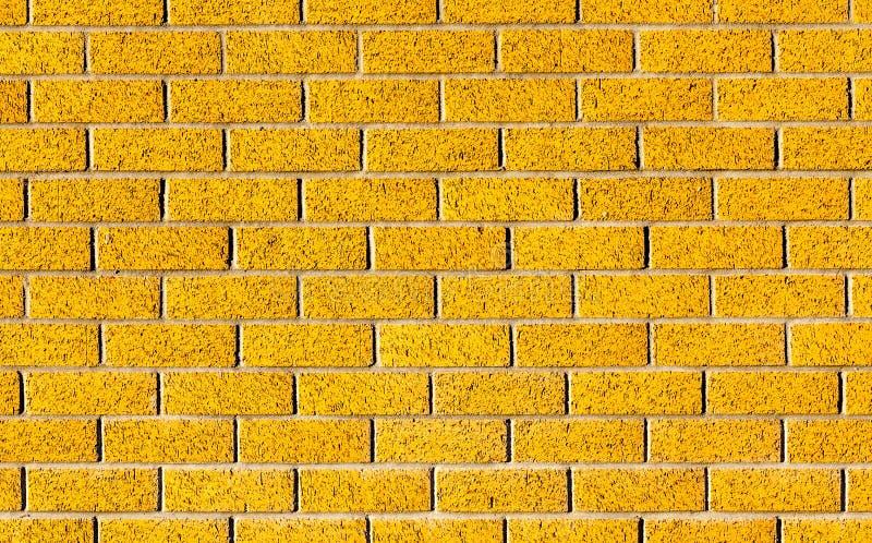 Driftig gul tegelstenvägg som en bakgrundsbild med svart vig arkivbilder