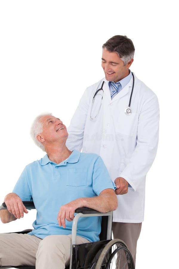 Driftig hög patient för doktor i rullstol fotografering för bildbyråer