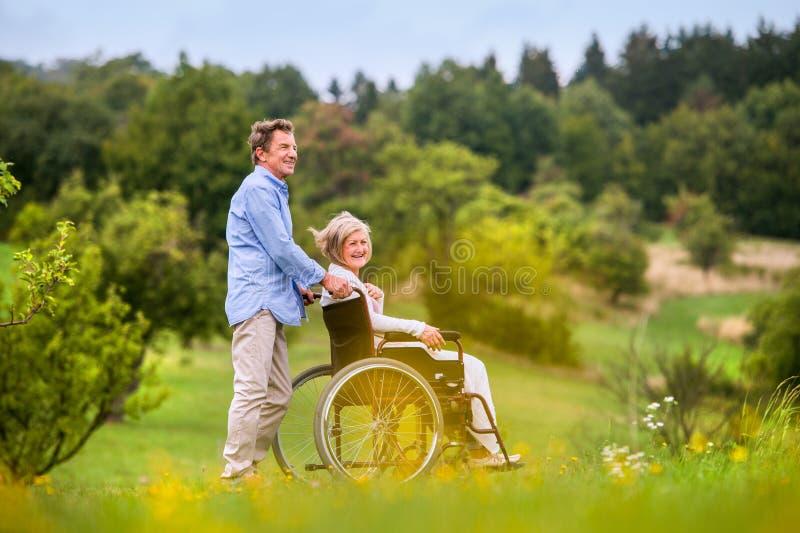 Driftig kvinna för hög man i rullstolen, grön höstnatur royaltyfri foto