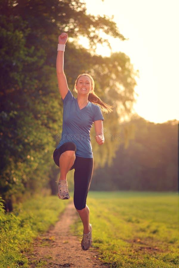 Driftig kvinna som hoppar i luften arkivbild