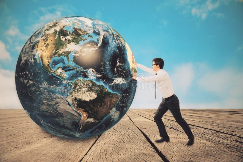Driftig planet för affärsman på trägolv royaltyfria bilder