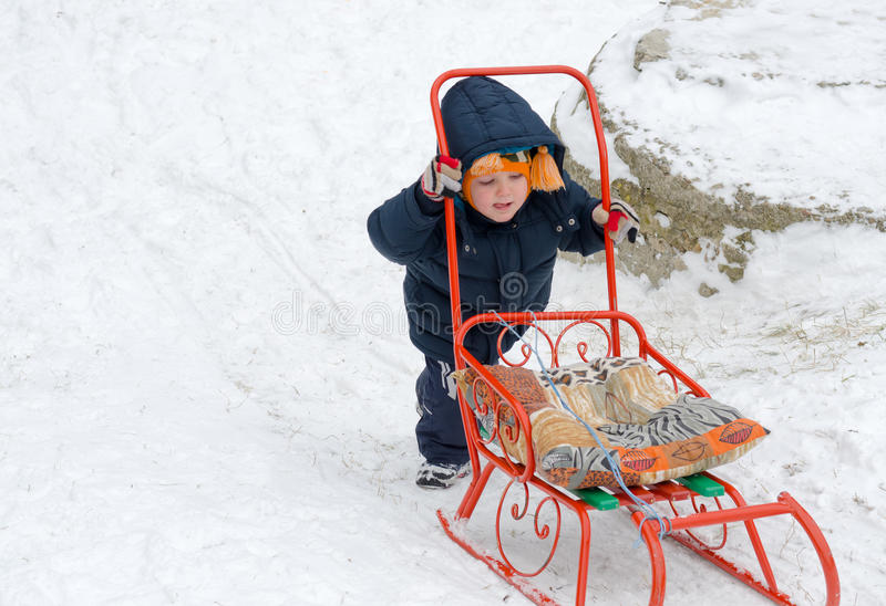 Driftig pys hans sled i snow arkivbild