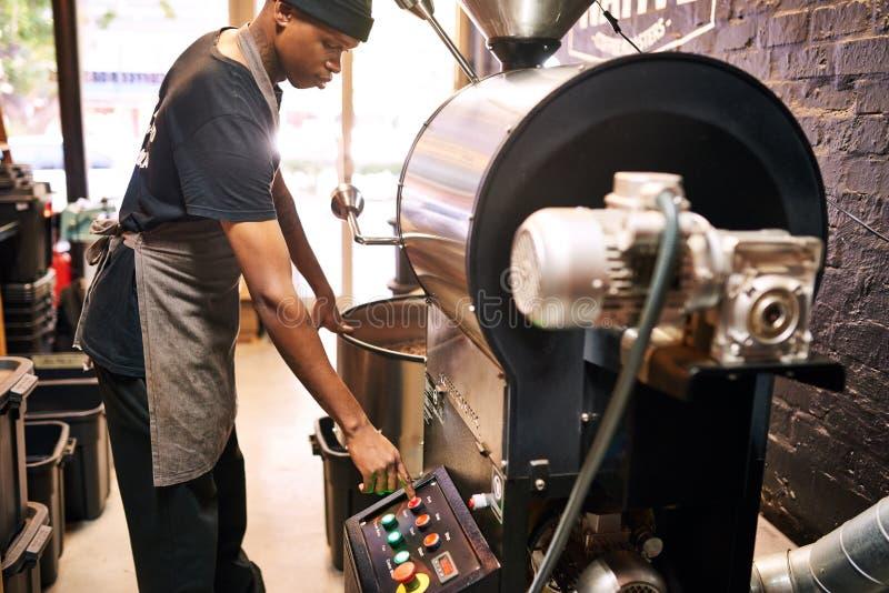 Driftig röd knapp för afrikansk man på en industriell kaffemaskin royaltyfri foto