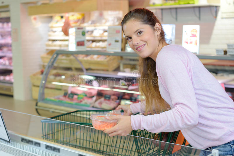 Driftig shoppingspårvagn för kvinna i supermarket royaltyfri bild