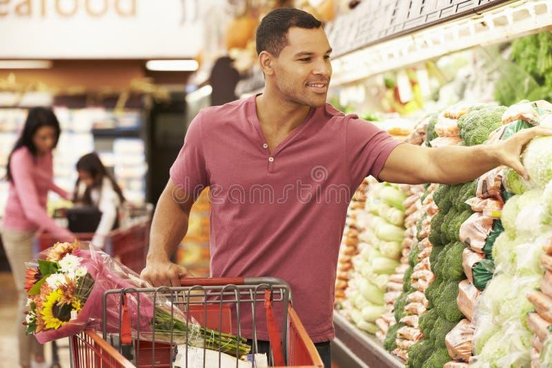 Driftig spårvagn för man vid jordbruksprodukterräknaren i supermarket arkivbilder