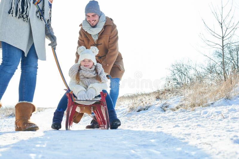 Driftigt barn för fader med släden i vinter arkivfoton