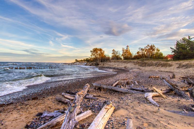 Autumn Driftwood Beach On Lake Superior. Driftwood beach on Lake Superior with the Whitefish Point Lighthouse. Whitefish Point is in the Upper Peninsula of stock photos