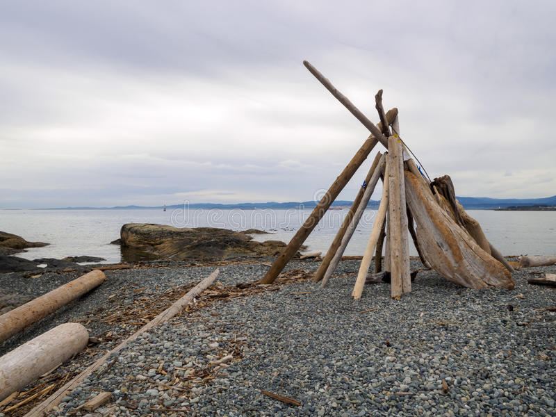 Driftwood Teepee tipi structure on a rock pebble beach by the water on the coastline. Teepee on the beach on a cloudy day stock photos