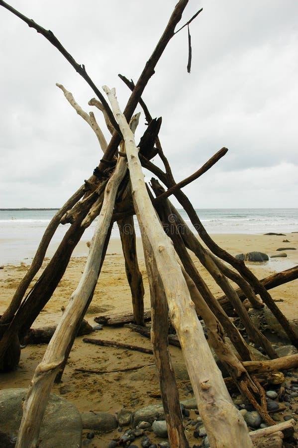Drijfhout in een tipi op een verlaten strand wordt gestapeld dat stock foto's