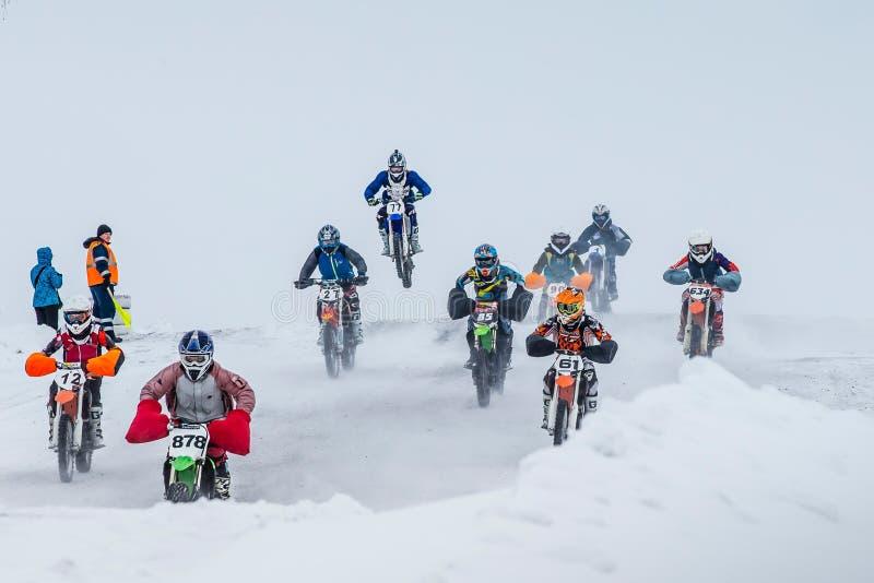 Drijven de groeps jonge ruiters op motorfietsen snow-covered motocrossspoor stock afbeelding