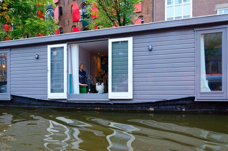 Drijvend huis bij kanaaldijk in historisch centrum van stad, Amsterdam, Nederland royalty-vrije stock afbeeldingen