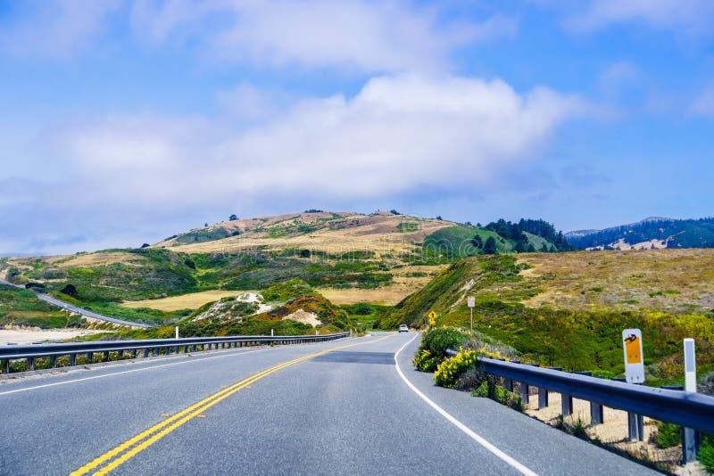 Drijvend op toneelweg 1 (Cabrillo-Weg) op de Vreedzame Oceaankustlijn dicht bij Davenport, Santa Cruz-zichtbare bergen stock foto
