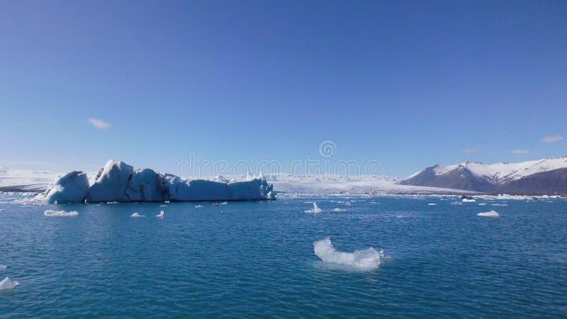 Drijvende Ijsbergen op Natuurlijke Blauwe Lagune en Bergenweergeven royalty-vrije stock foto
