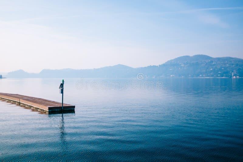 drijvende pier met achtergrond het meer en de bergen op een brigh royalty-vrije stock afbeelding