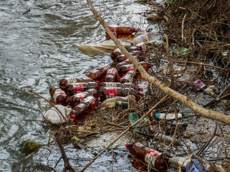 Drijvende plastic bierflessen in de kleine rivier royalty-vrije stock foto's