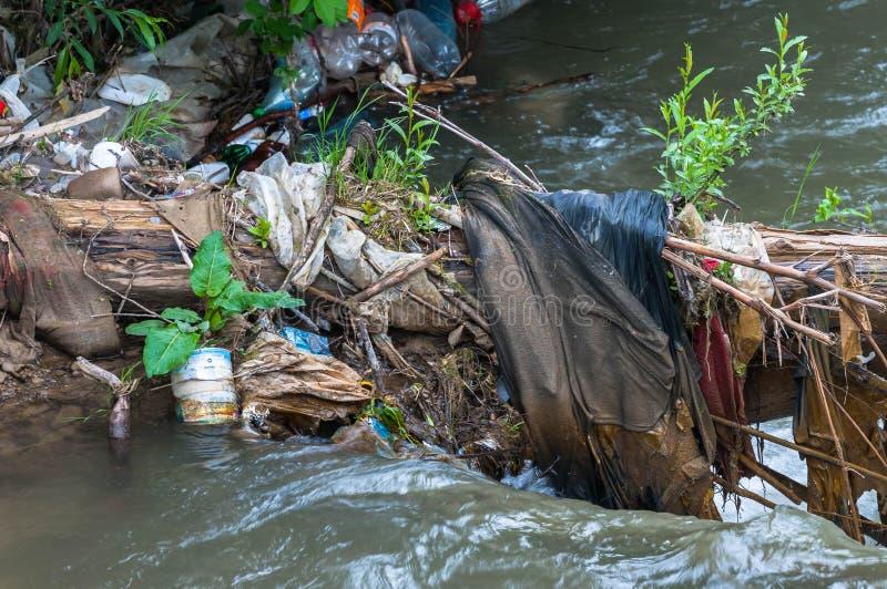 Drijvende plastic flessen, menselijk huisvuil in de kleine rivier royalty-vrije stock foto's