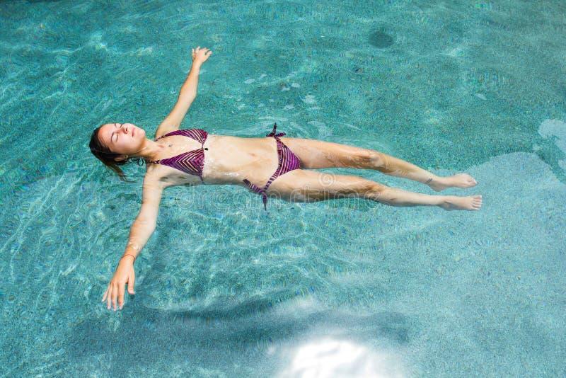 Drijvende vrouw in de pool stock foto