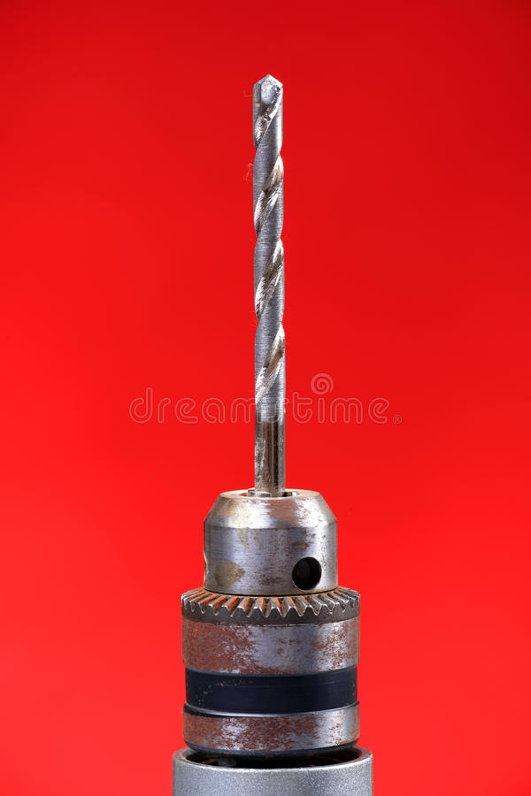 Drill bit. Closeup shot of drill bit with red background stock photos
