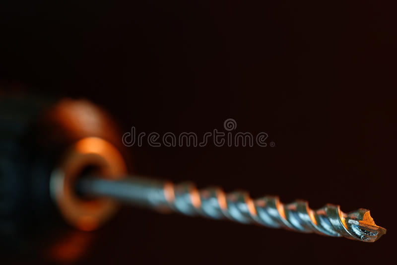 Drill Bit. Electric drill and bit in close-up with shallow depth of field. 36 mp image against black stock photography
