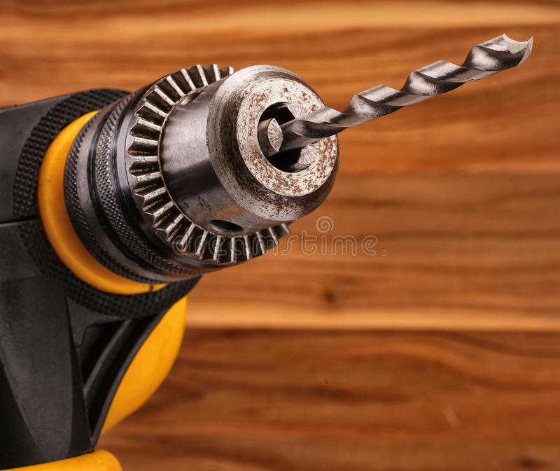 Drill with drill bit. Electric drill with drill bit on a wooden background stock photo