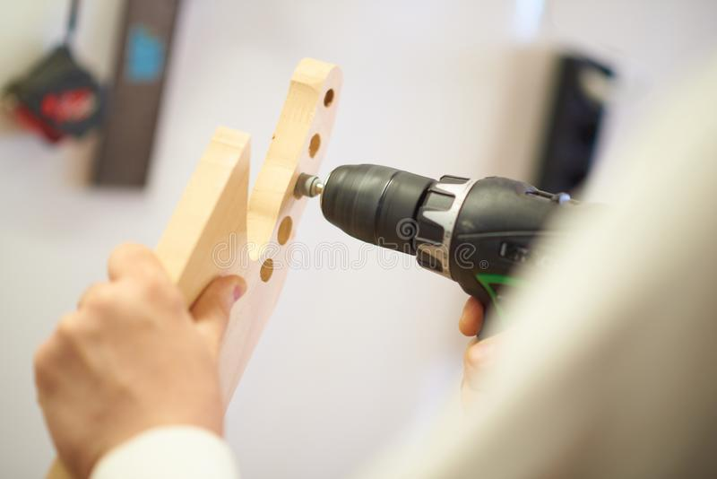 Drill in the hands in the process of grinding products royalty free stock photo