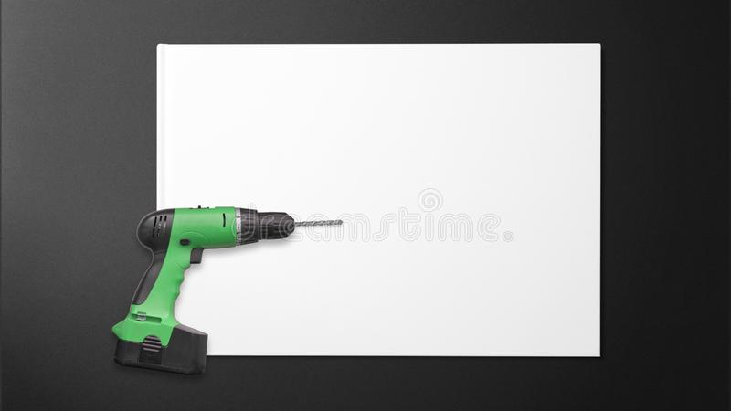 Drill machine on paper on black background royalty free stock photos