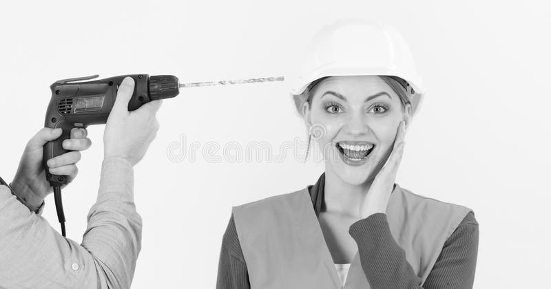 Drill makes hole in female head. Stress resistance concept. Lady happy and carefree. Male hands with drill drills head royalty free stock photos