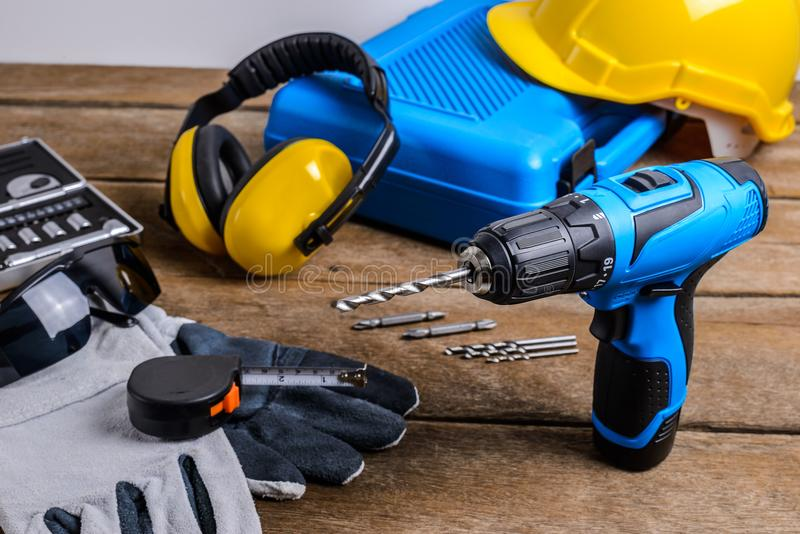 Drill and set of drill,tools,carpenter and safety, Protection Equipment. On wooden table background royalty free stock image