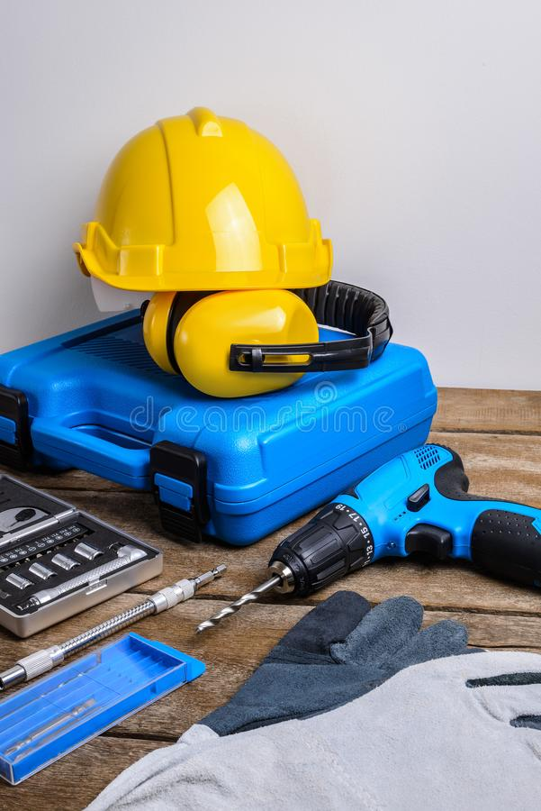 Drill and set of drill,tools,carpenter and safety, Protection Equipment. On wooden table background stock image