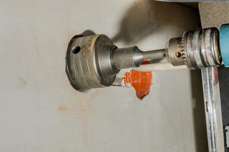 Drillborren borrar ett hål i en betongvägg för ett elektriskt uttag royaltyfri bild