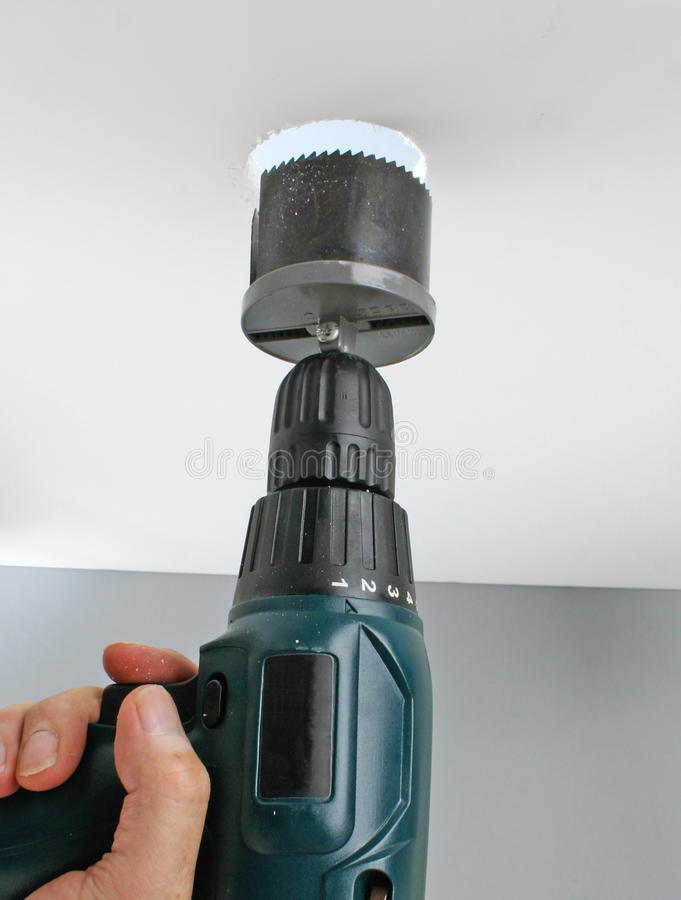 Drilling a hole in the ceiling stock images