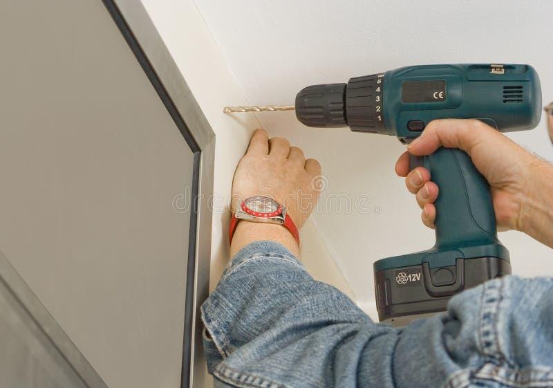 Drilling a hole for a curtain rail. Handyman drilling a hole for a curtain rail stock image