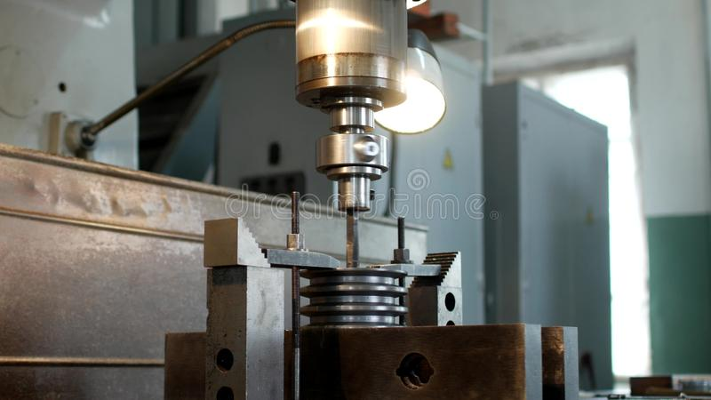 Drilling a hole with a drilling machine in a metal workpiece pulley, close-up, industry, manufacturing pulley royalty free stock photo