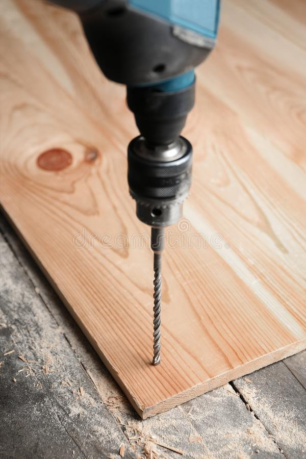 Drilling hole in wooden board royalty free stock images