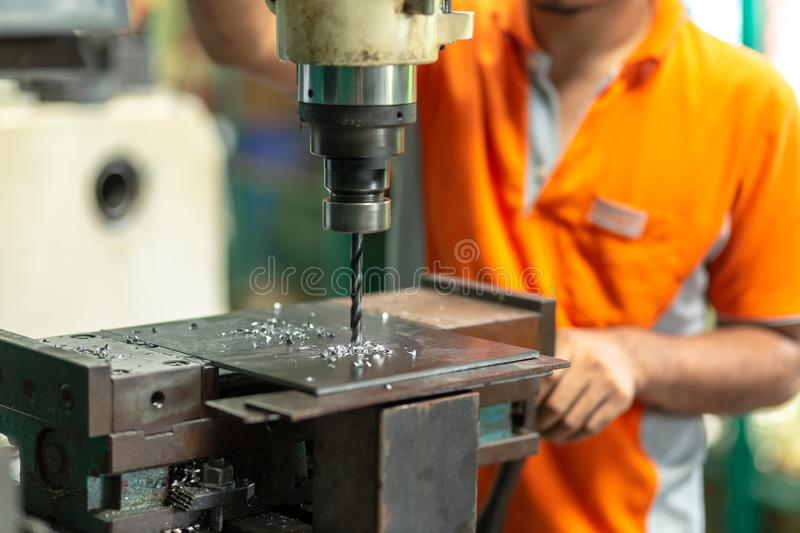 DRILLING MACHINE, Employee drilling machine in flat steel plate. With bench drill stock images