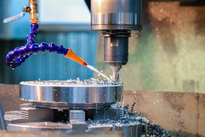 Drilling machine makes a hole in the metal product. Coolant is pouring on the drill stock photo