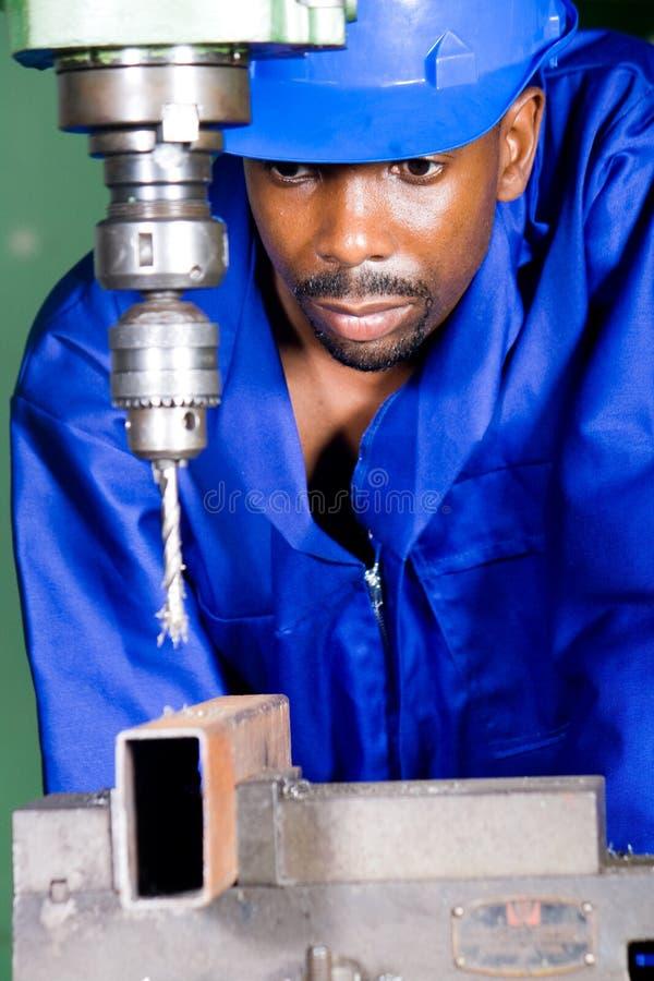 Drilling machine operator. African american machinist operator operating a drilling machine royalty free stock image
