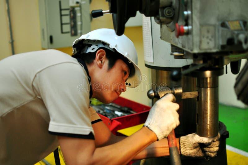Drilling machine operator. Thai machinist operator operating a drilling machine royalty free stock photos
