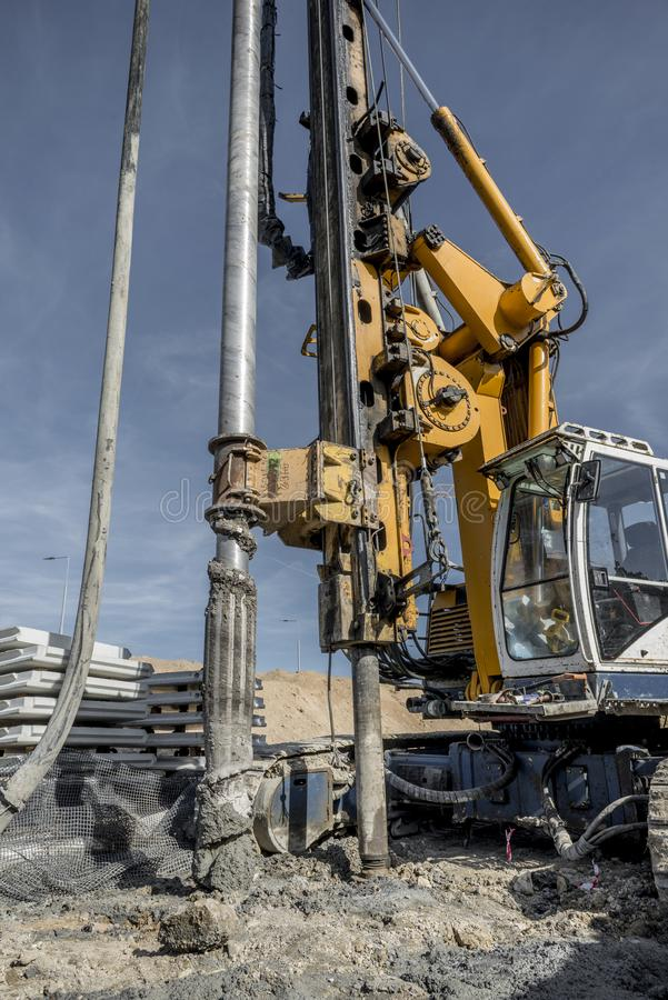 Drilling machine ready to drill piles on a road building site royalty free stock photo