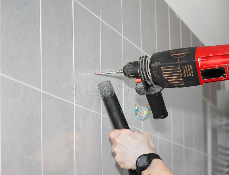 Drilling. A marked tile wall to install bathroom fittings stock images