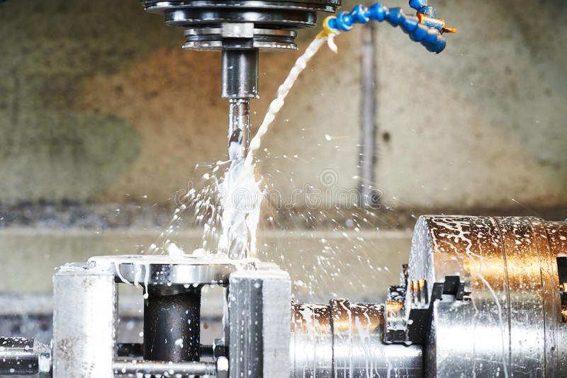 Drilling process of metal on machine tool. Drilling hole or boring detail with lubricant liquid coolant on metal cutting machine tool at factory stock image