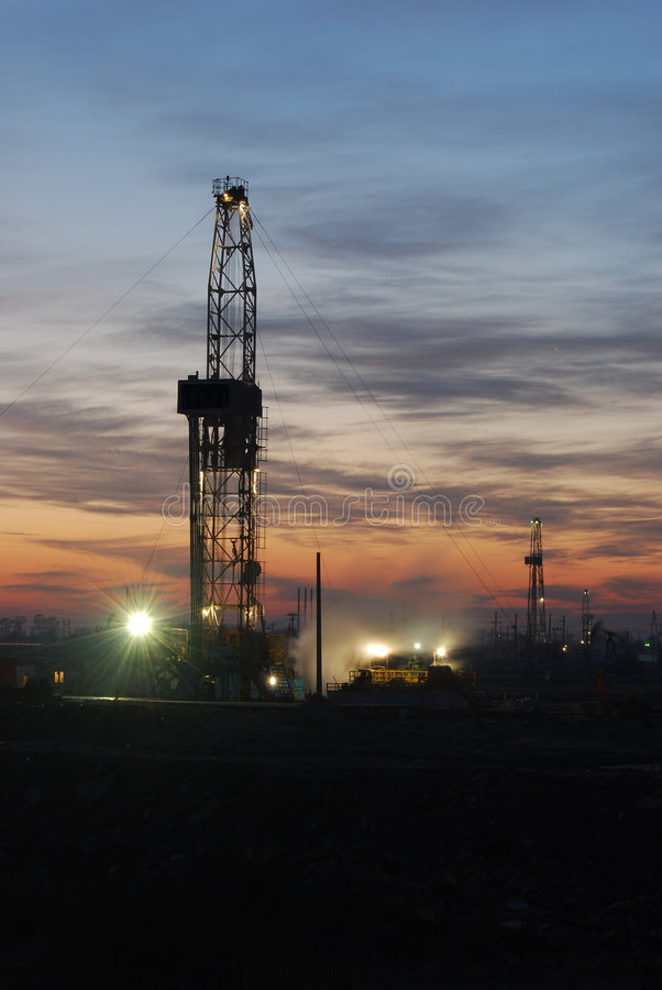 Drilling rig. Sunset glow night scenes industries Oilfield landscape royalty free stock image