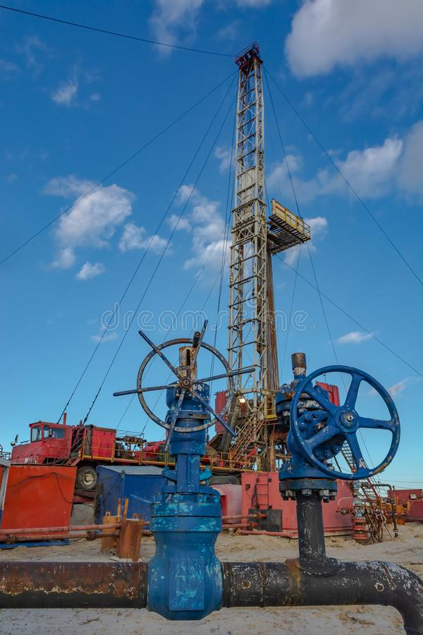 Drilling rig for deep drilling in oil and gas. The design of the drilling rig for deep drilling in oil and gas against a blue sky. Many drill pipes installed royalty free stock images