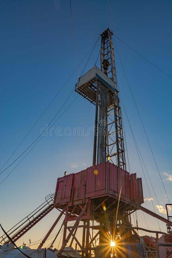 Drilling rig for deep drilling in oil and gas. Drilling rig for deep drilling for oil and gas with a sunbeam at the base. The image of bursting energy of the royalty free stock photo