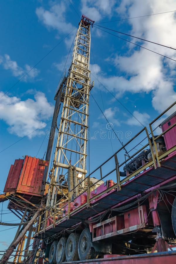 Drilling rig for deep drilling in oil and gas. The design of the drilling rig for deep drilling in oil and gas against a blue sky. Many drill pipes installed stock photography