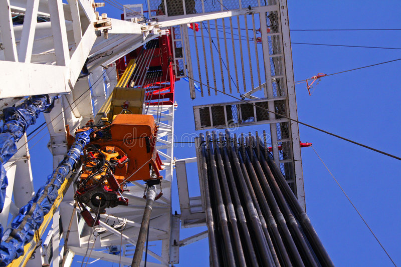 Drilling rig floor upward. An upward view of a large drilling rig with pipe racked on the floor royalty free stock images