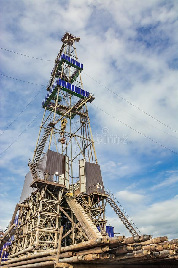 Drilling rig for drilling oil and gas wells with drill pipes in the foreground. Drilling rig for drilling wells in the northern field for the extraction of oil royalty free stock photography