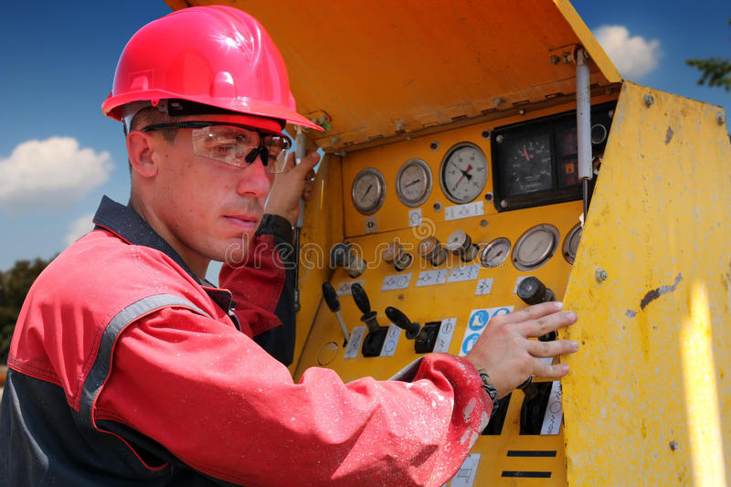 Drilling Rig Worker. Oil and gas well drilling worker operate drilling rig machinery. Selective focus stock photography