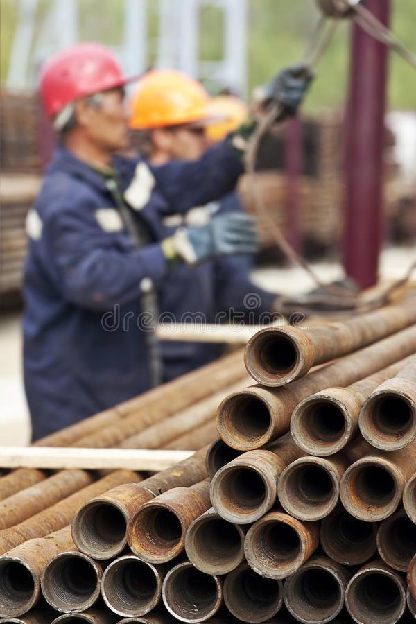 A drilling rig workers. Focus is on the pipes stock image